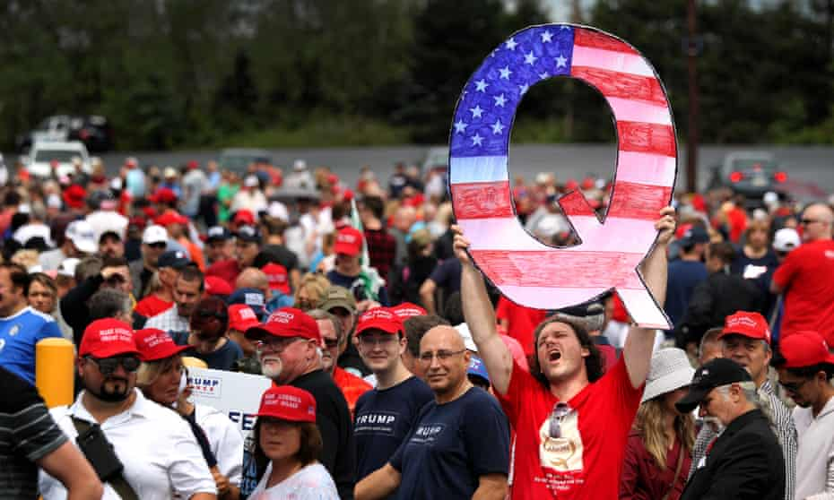 A man holds up a large 'Q' sign while waiting in line for a Trump rally in Wilkes-Barre, Pennsylvania.