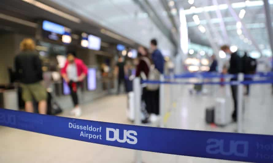 Tourists at Dusseldorf airportwait to check in for a flight to Mallorca.