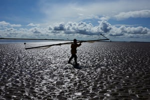 Owen carrying net across the sand