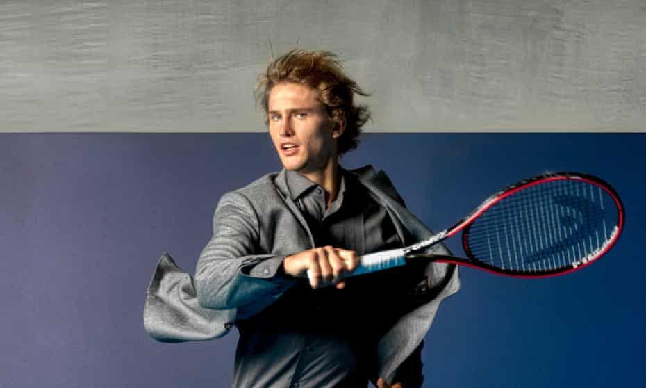 Alex Zverev in a shiny grey smart-casual suit and shirt, and white trainers, mid-stride, and holding a racquet as if he's just hit a tennis ball