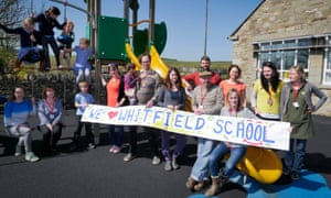 Parents hold banner saying 'we love Whitfield school'