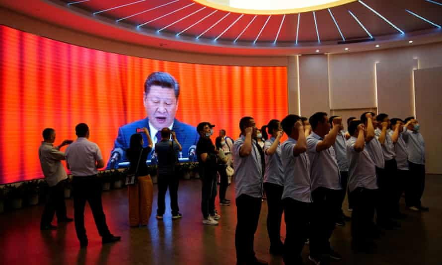 People recite the Communist party oath in front of a screen dominated by an image of Chinese president Xi Jinping.