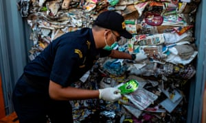 An Indonesian customs officer inspects a container filled with garbage originating from Australia, which should have contained only waste paper, but authorities also found hazardous material