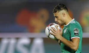 Algeria forward Youcef Belaili kisses the ball during the penalty shootout victory against Ivory Coast.