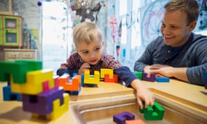 Man and child playing with blocks in a science center