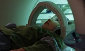 A child enters a mini MRI machine for a brain scan.