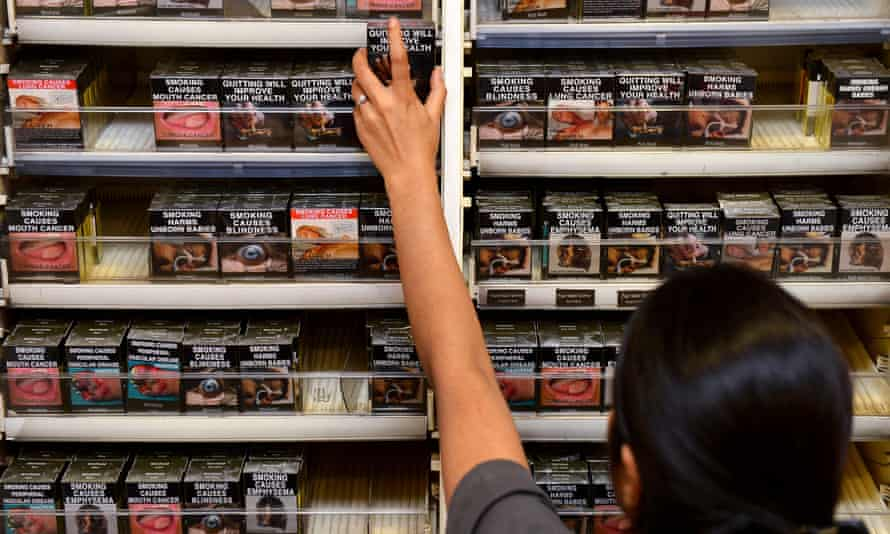 a person reaches for a pack of cigarettes stacked high on a shelf
