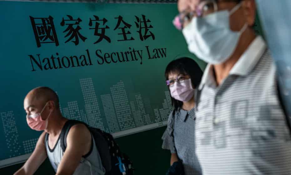 Masked pedestrians walk past government ad