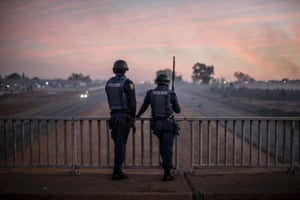 Anti-riot policemen stand guard on a bridge as protesters block a highway during a protest ahead of the August municipal elections in Meyerton, South Africa