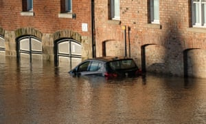 A parked car surrounded by water after levels rose in York, England.