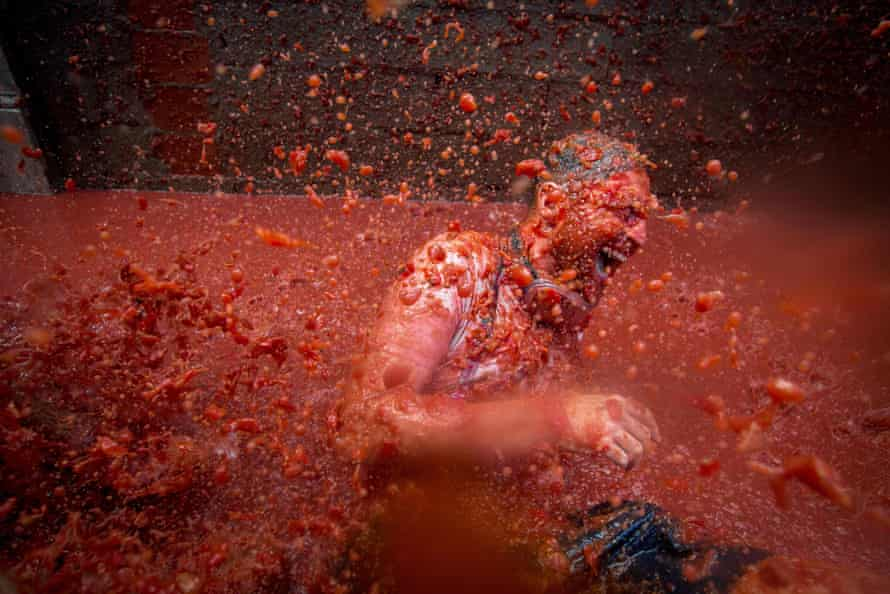 A reveller is pelted with tomato pulp during the annual Tomatina festivities in the village of Buñol, near Valencia.