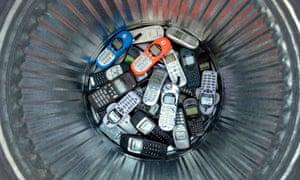 old mobile phones in a metal dustbin