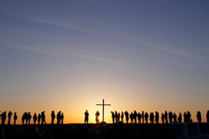 People silhouetted as the sun rises during a dawn service to celebrate Easter Sunday.