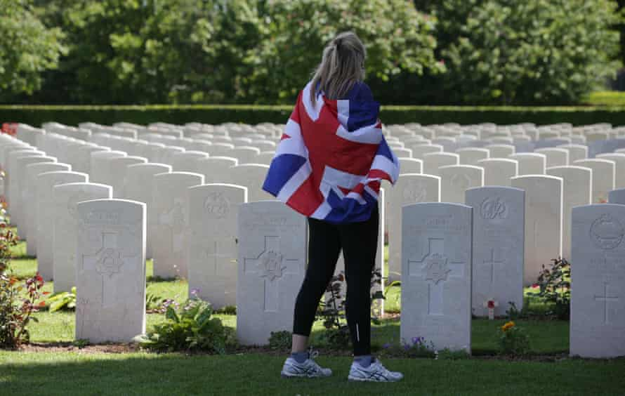 A visitor draped in a union flag walks among the headstones at the Bayeux cemetery.
