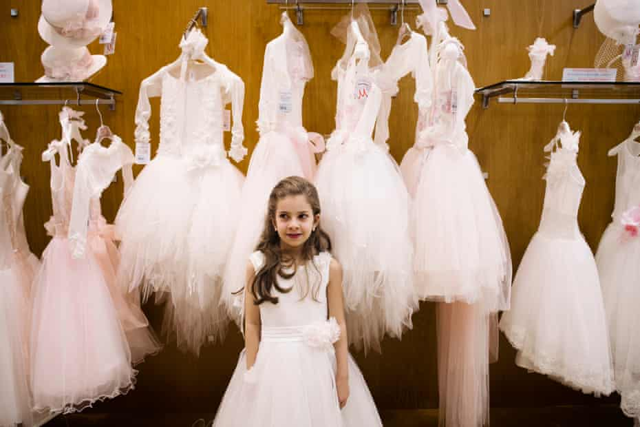Irene poses during dress rehearsals for her first holy communion in the historic Naples shop Fratelli Martone, a specialist for a century in ceremonial clothing for children.