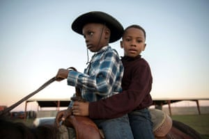 Two young boys riding a horse