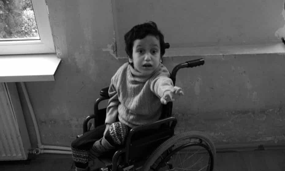 A child sits in a wheelchair, reaching for the photographer