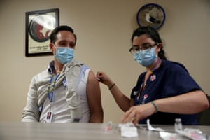 Colleen DAmico (R), a clinical pharmacist with Seattle Indian Health Board (SIHB), administers a shot of the Moderna COVID-19 vaccine, to Ryan Gilbert (L), Chief Operating Officer at the SIHB.