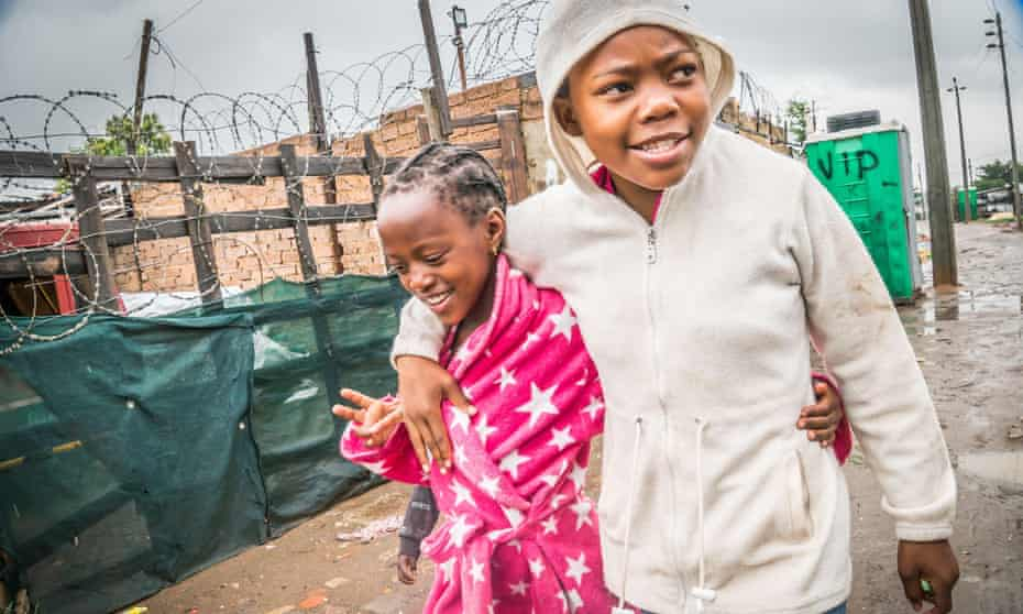 Two girls walk down a street in an impoverished area of Soweto.