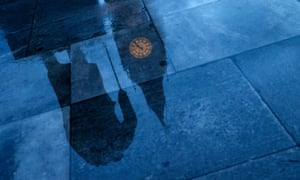 A statue of Winston Churchill is reflected in the rain covered pavement in front of the Houses of Parliament.
