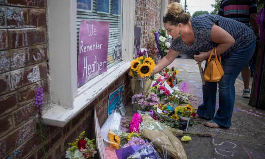 People lay flowers at the memorial for Heather Heyer on the street where she was struck and killed last year, in downtown Charlottesville, Virginia.