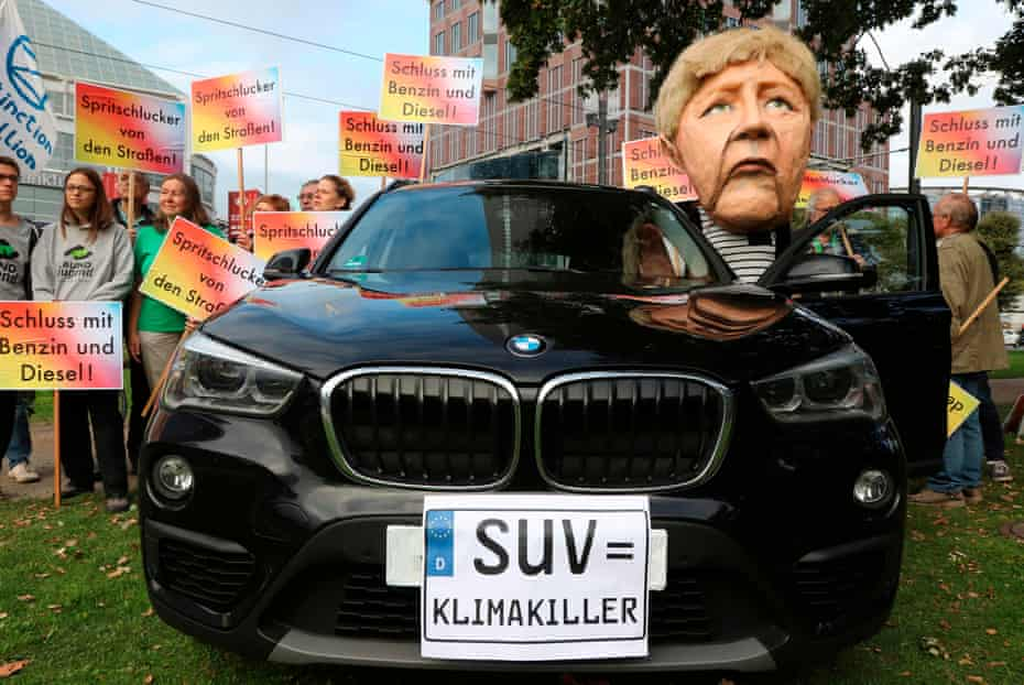 Activists, including one wearing a Angela Merkel mask, outside the Frankfurt International Auto, holding signs reading 'gas guzzling vehicles off the road' and 'Stop petrol and diesel'.