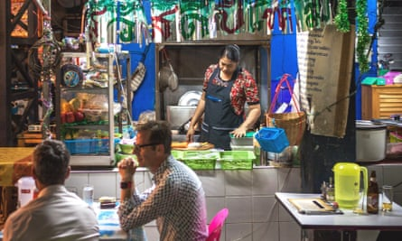Two customers sit outside the Burmese Restaurant and Library while a chef works at the street food cart, in Chiang Mai, Thailand