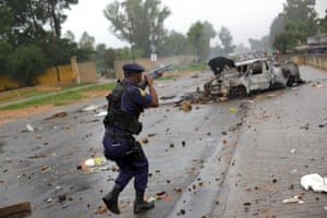 A South African policeman fires rubber bullets at residents of Zandspruit, an informal settlement west of Johannesburg, who had barricaded roads after their illegal electricity supply was shut down by the authorities.