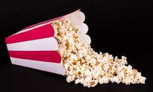 Spilled box of popcorn on black background