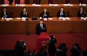 China's President Xi Jinping stands after placing his ballot in a box during a vote on an amendment to the constitution