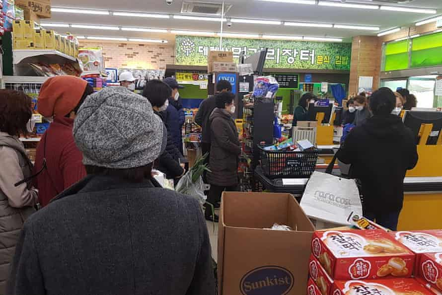 People line up to buy foods and supplies at a supermarket in Daegu, South Korea, on Friday