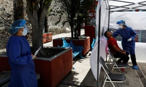 A health worker in personal protective equipment (PPE) conducts a coronavirus test in the municipality of Tlahuac, one of the highly contagious zones of the city