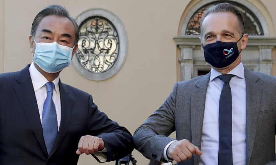 China's foreign minister, Wang Yi and the German foreign minister, Heiko Maas, touch elbows. They are both wearing face masks