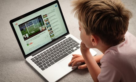 A boy watches a YouTube video on a laptop computer