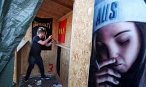 A man demolishes a marijuana stall in Christiania