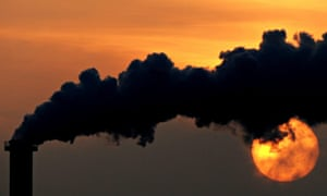 The sun sets behind a smoking chimney in Wismar, Germany.