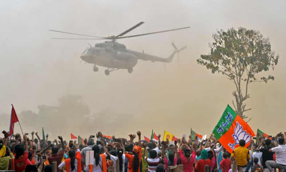 Supporters wave towards a helicopter carrying the Indian prime minister, Narendra Modi, at a rally for West Bengal's state legislative assembly elections, at Kawakhali on the outskirts of Siliguri, on April 10