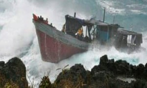A wooden fishing boat is driven on to the rocks of Christmas Island on 15 December 2010