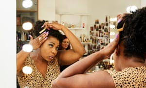 Brenda Edwards seen in the mirror of her dressing room as she puts a clip in her hair