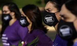 Women wear masks with the phrase 'women overthrow Bolsonaro' written on them, during a protest against the government's inefficiency over the pandemic, in Brasilia, Brazil.