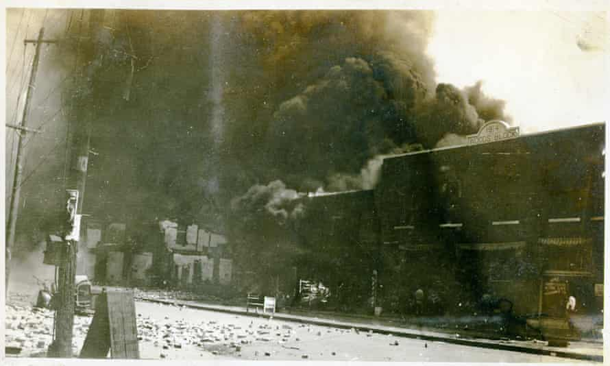 Damaged properties and smoke coming from buildings following the Tulsa race massacre, in Tulsa, Oklahoma, on June 1921.