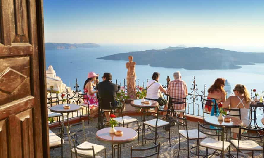 Thira (capital of Santorini) - tourists resting on the greek cafe restaurant terrace, Santorini Island, Greece