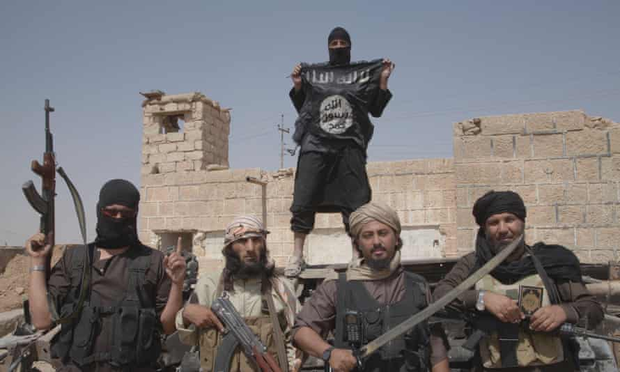 A group of Islamic State fighters brandishing flags and weapons
