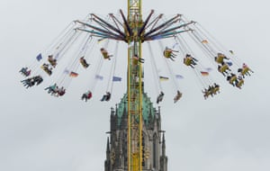 Visitors on a funfair ride in front of St Paul's church in Munich