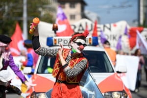Zurich, Switzerland. A protester dressed as a clown marches in front of a police vehicle