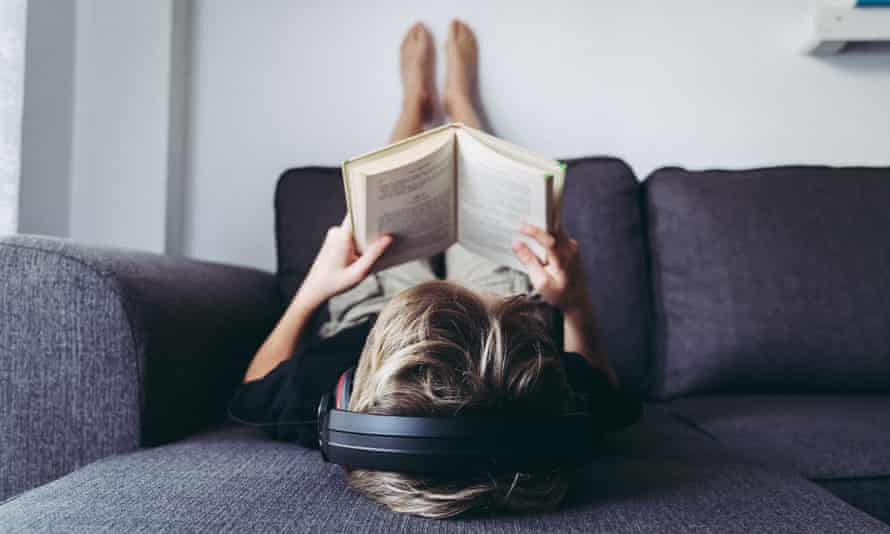 Boy listening to music while reading book on sofa at home