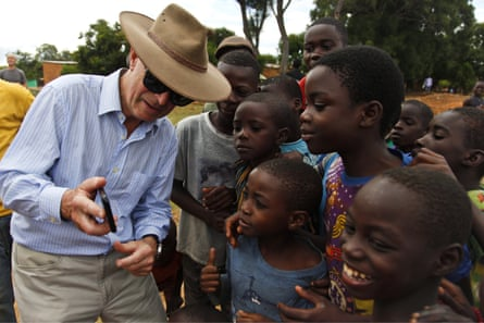 The former chief of the UK armed forces, General Lord Richards, shows a photograph to children in northern Zambia during a visit to the last battleground of WWI in Africa.