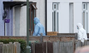 Forensics investigators enter a property being searched in Sunbury, Surrey.