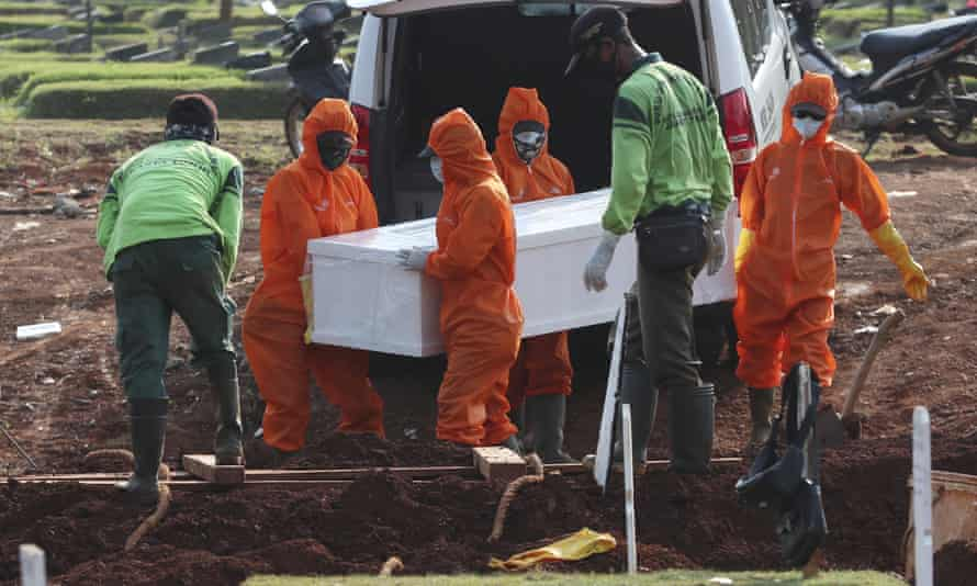 Workers in protective suits carry a coffin containing the body of someone who may have died of Covid-19 for burial at a special cemetery in Jakarta.