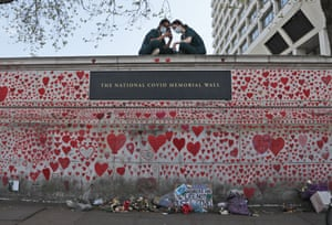 Nurses from the nearby St Thomas' hospital sitting on the National Covid Memorial Wall in London today.